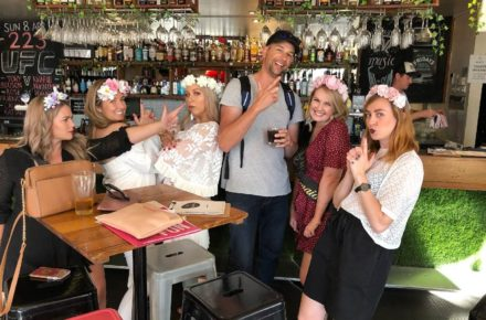 A group of hens in flower crowns having cheeky fun in a pub in Northbridge.